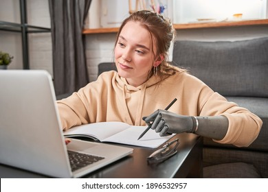 Beautiful young woman with prosthesis arm writing at notebook while sitting at the table with her laptop computer. Adorable girl looking at the screen while working at home