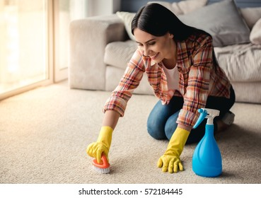 Beautiful young woman in protective gloves is smiling, using a detergent and a brush while cleaning carpet at home