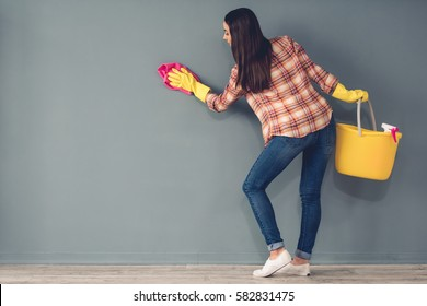 Beautiful young woman in protective gloves is cleaning a wall