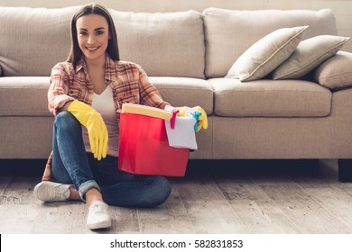 Beautiful young woman in protective gloves is holding a bucket with things for cleaning, looking at camera and smiling while sitting on the floor at home