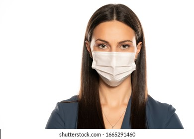 Beautiful young woman with protective mask on her face on white background