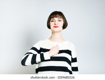 beautiful young woman is proud of herself, short haircut, wears a sweater, studio photo on the background