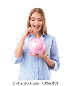 Beautiful young woman putting coin into piggy bank, on white background