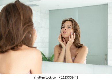 Beautiful young woman putting cream on face skin. Pretty girl touching cheek with hand. Charming female character looking at mirror. Home bathroom. Facial health. Skincare and hygiene. Daily makeup
