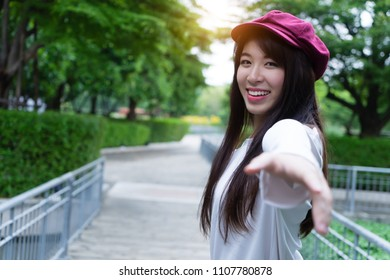 Beautiful young woman reaching hand back to boyfriend. leading girl walking follow lover. couple in love in nature vacation time