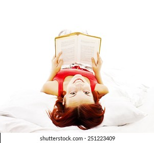 Beautiful young woman reading book in bed. Isolated on white background