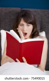 Beautiful young woman reading a book with a astonish expression