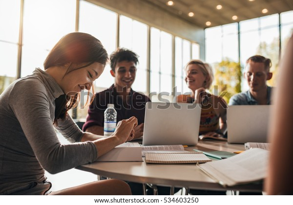 Beautiful young woman reading book with classmates studying in background. University students studying together in class.