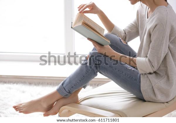 家の窓際で本を読む美しい若い女性
