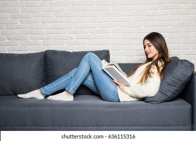 Beautiful young woman reading magazine and lying on sofa at home