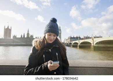 Beautiful young woman reading text message through smart phone by river Thames; London; UK