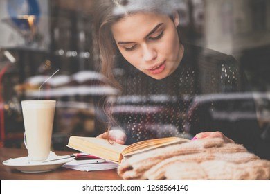 Beautiful young woman reads a book in cafe. View behind the window glass.