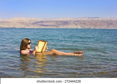 beautiful young woman reads a book floating in the waters of the Dead Sea in Israel