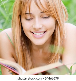 Beautiful young woman reads book, on green summer background.