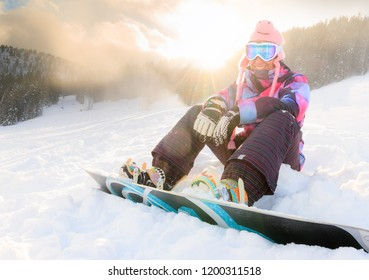 Beautiful young woman ready to snowboard on the snowy ski slopes on a sunny day in the Alps in the Brandnertal, Vorarlberg Austria