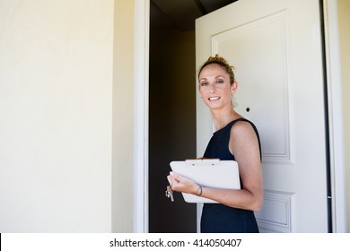 beautiful young woman real estate agent in front of a house for sale