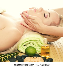 A beautiful young woman receiving facial massage at a spa salon. Perfect Skin. Skincare. Young Skin