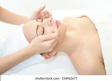 Schöne junge Frau, die Gesichtsmassage in einem Spa-Salon erhält
