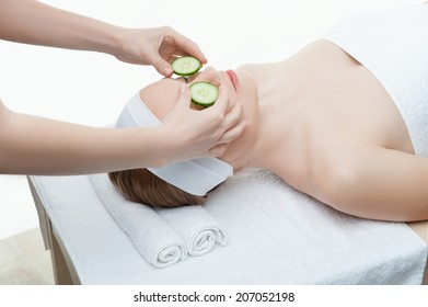 Beautiful young woman receiving facial mask of cucumber in beauty salon, hands of cosmetologist, isolated on white