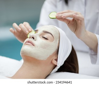 Beautiful young woman receiving facial mask of cucumber in beauty salon, hands of cosmetologist