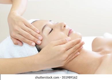 Beautiful young woman receiving facial massage