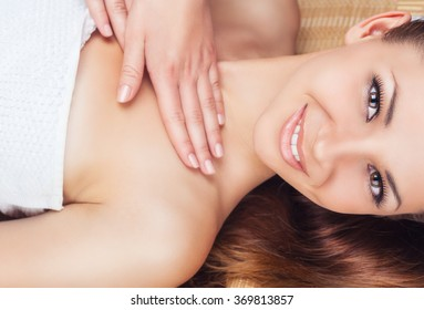 Beautiful young woman receiving facial and neck massage in a spa salon