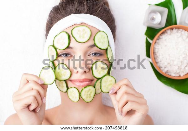 Beautiful young woman receiving facial mask of cucumber