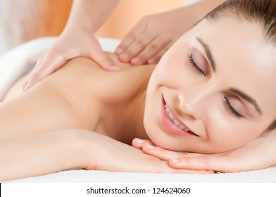 Beautiful young woman receiving hand massage on her back at beauty spa salon