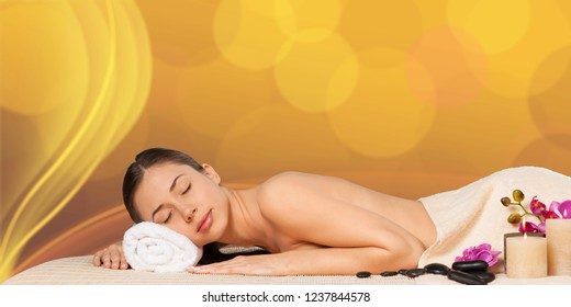 Beautiful young woman receiving hot stone massage at salon spa