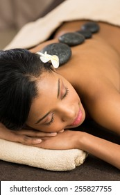 Beautiful young woman receiving hot stone massage at spa