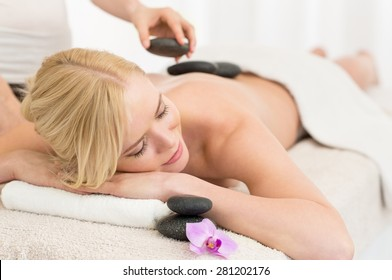 Beautiful young woman receiving hot stone massage at salon spa
