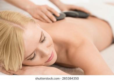 Beautiful young woman receiving hot stone massage