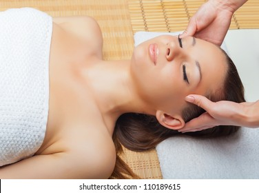 Beautiful young woman receiving massage of head in spa salon
