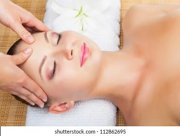 Beautiful young woman receiving massage of head in beauty salon