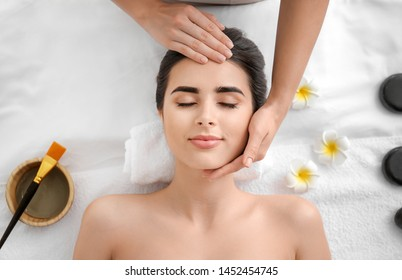 Beautiful young woman receiving massage in spa salon