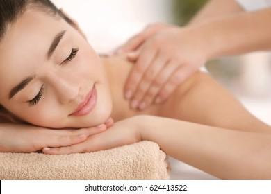 Beautiful young woman receiving massage in spa salon, closeup