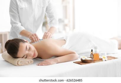 Beautiful young woman receiving scrub massage in spa salon
