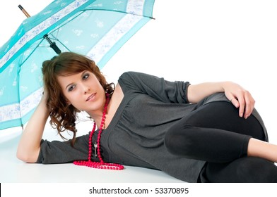Beautiful young woman reclining under an umbrella against a white background and reflective floor.