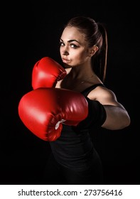 Beautiful young woman in a red boxing gloves over black background