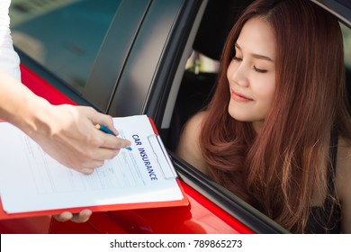 Beautiful young woman in red car is talking to car insurance salesman.  Car insurance concept.