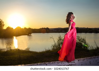 Beautiful young woman in a red dress in the summer field