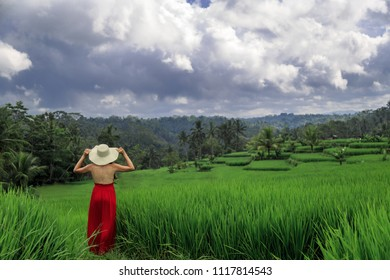Beautiful young woman in red dress touch straw hat. Girl walk at typical Asian hillside with rice farming, mountain shape green cascade rice field terraces paddies. Ubud, Bali, Indonesia.