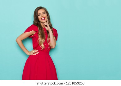 Beautiful young woman in red dress is holding hand on chin, looking at camera and talking. Three quarter length studio shot on turquoise background.