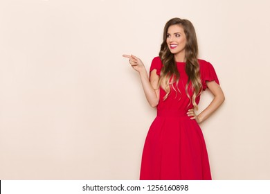 Beautiful young woman in red dress is smiling, looking away and pointing. Three quarter length studio shot on beige background.