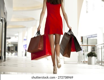 Beautiful young woman in a red dress, holding shopping bags walking in the shop