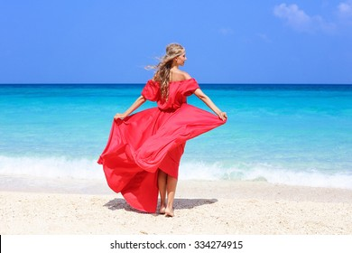 Beautiful young woman in red dress on a tropical beach. Blue sea on the background.