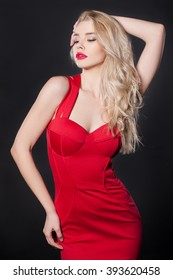 Beautiful young woman in a red dress on a black background. Black background, image Pretty woman.