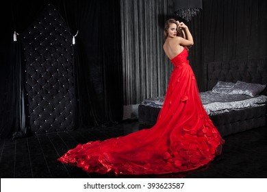 Beautiful Young Woman in a Red Dress, Background interior. Attractive Model of a brown-haired woman in a long red dress, black interior. Stylish Girl in a Long Dress in full growth