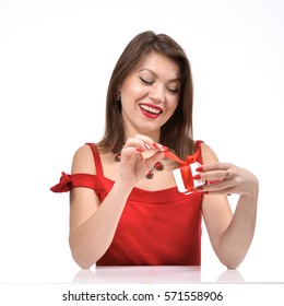 A beautiful young woman in a red dress with a gift. Valentines day. Photo on a white background.