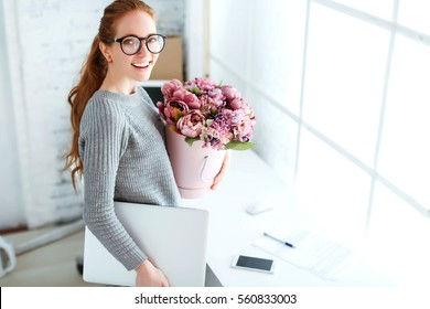 Beautiful young woman with red hair, an office worker at the workplace with a bouquet of flowers